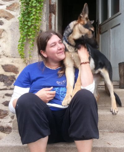 Natascha pets her German Shepard dog.