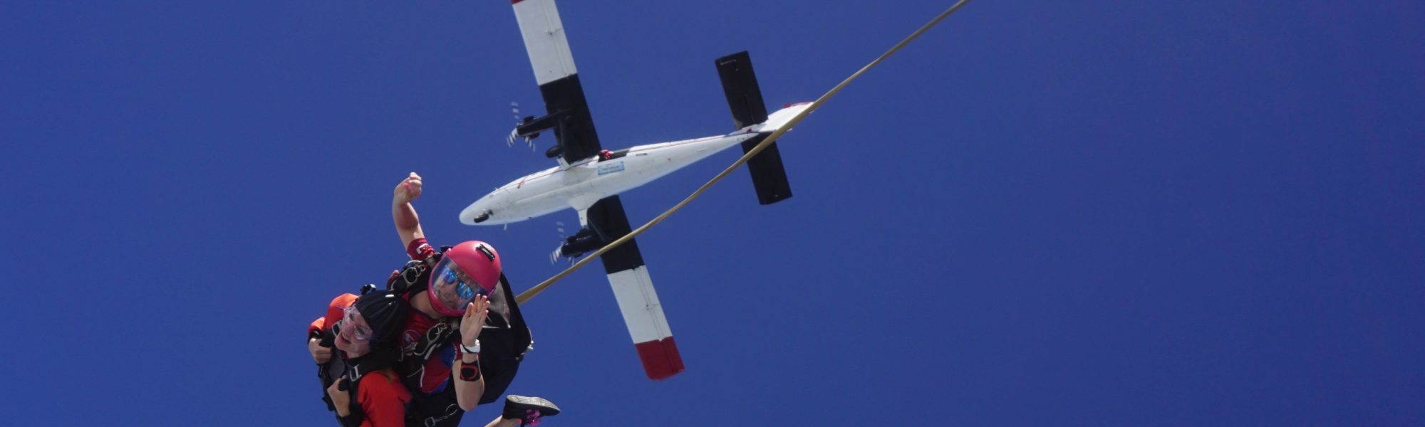 A tandem instructor deploys the drogue in free fall during a skydive
