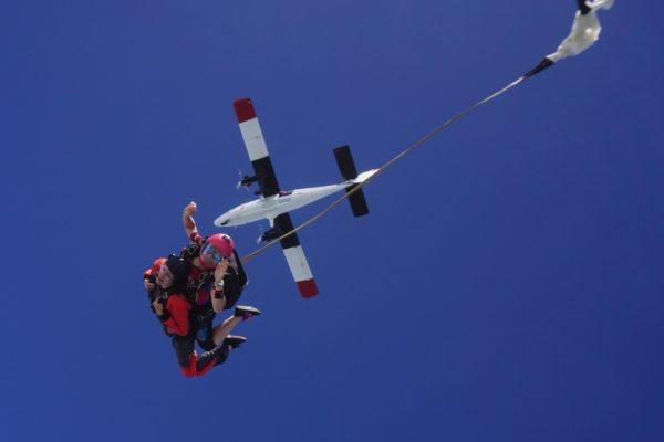 A tandem skydiving instructor deploys the drogue in free fall during a skydive