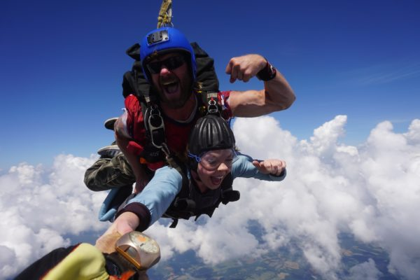 Tandem skydive instructor, Dave flexes his muscles in free fall with his student.