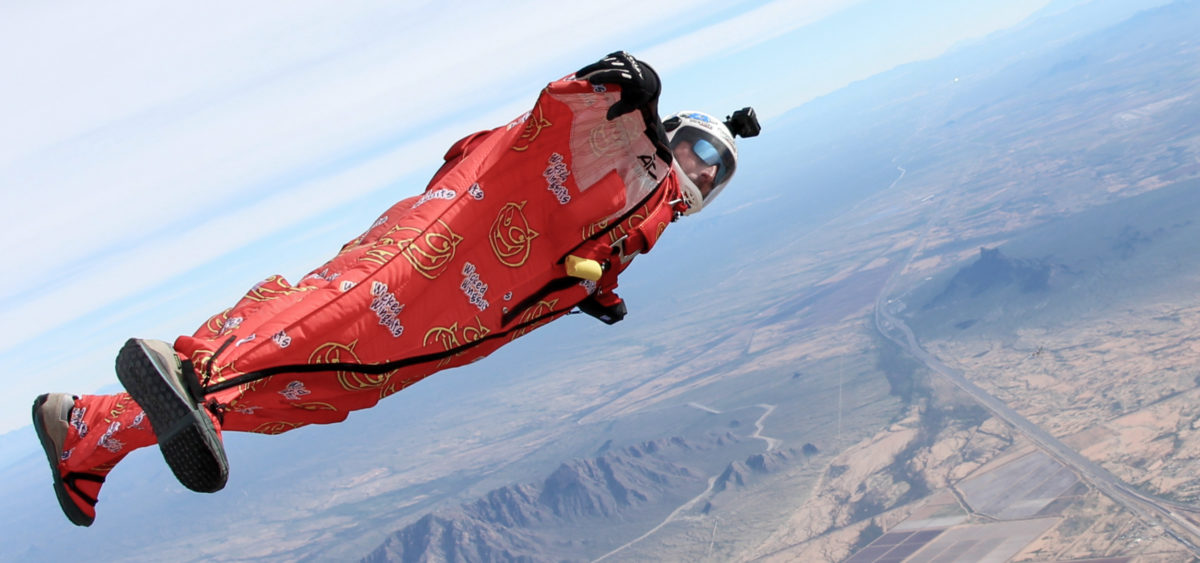 A man flies across the sky in a red wingsuit