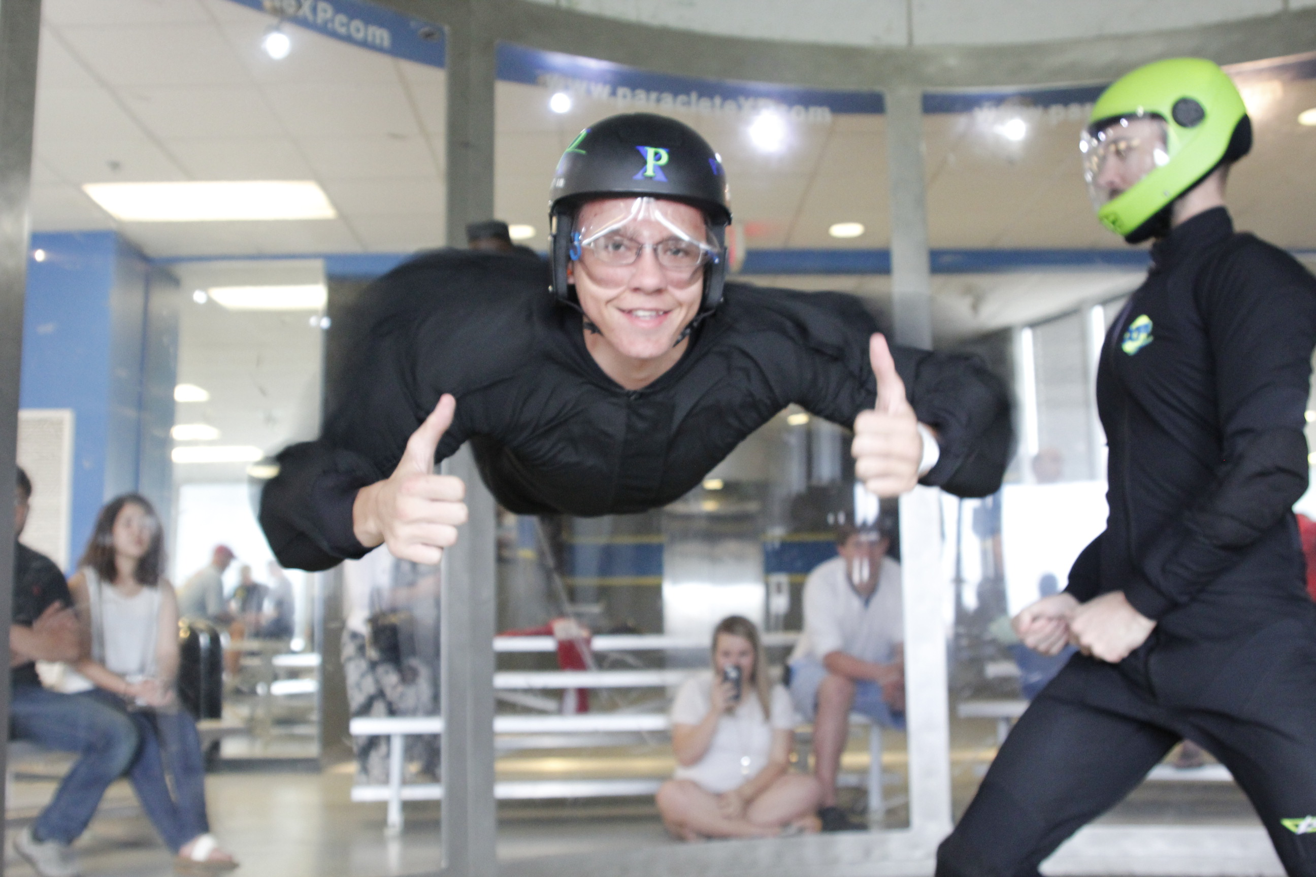 A man gives a thumbs up while flying at Paraclete XP Indoor Skydiving