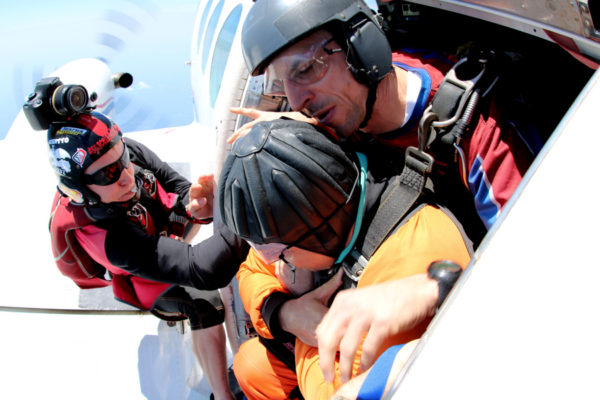 A tandem student sits in the door of the plane about to jump from 14,000'