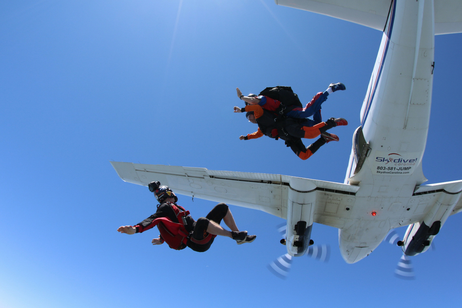 A camera flyer captures the perfect exit shot of a tandem pair from 14,000'