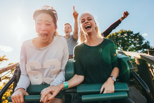 girls about to experience stomach drop on roller coaster ride