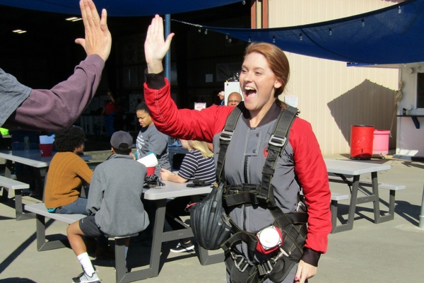 Mary Margaret Crews high fives someone after skydiving