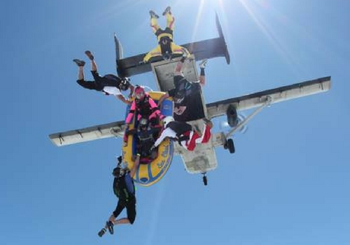 experienced skydivers exit plane with raft