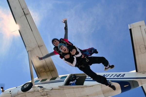 tandem skydiving student exiting jump plane