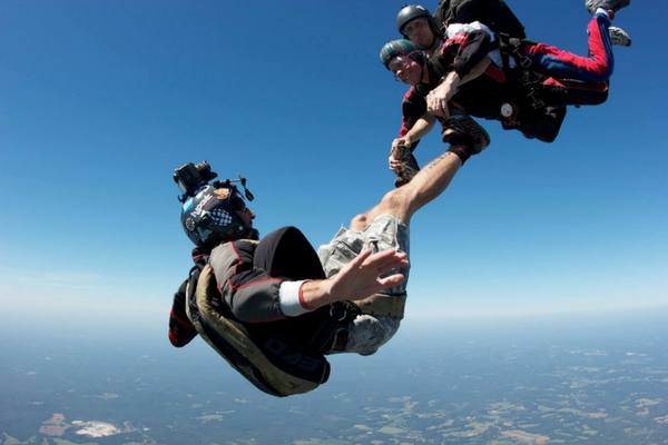 tandem skydiving student holds on to videographers feet during freefall
