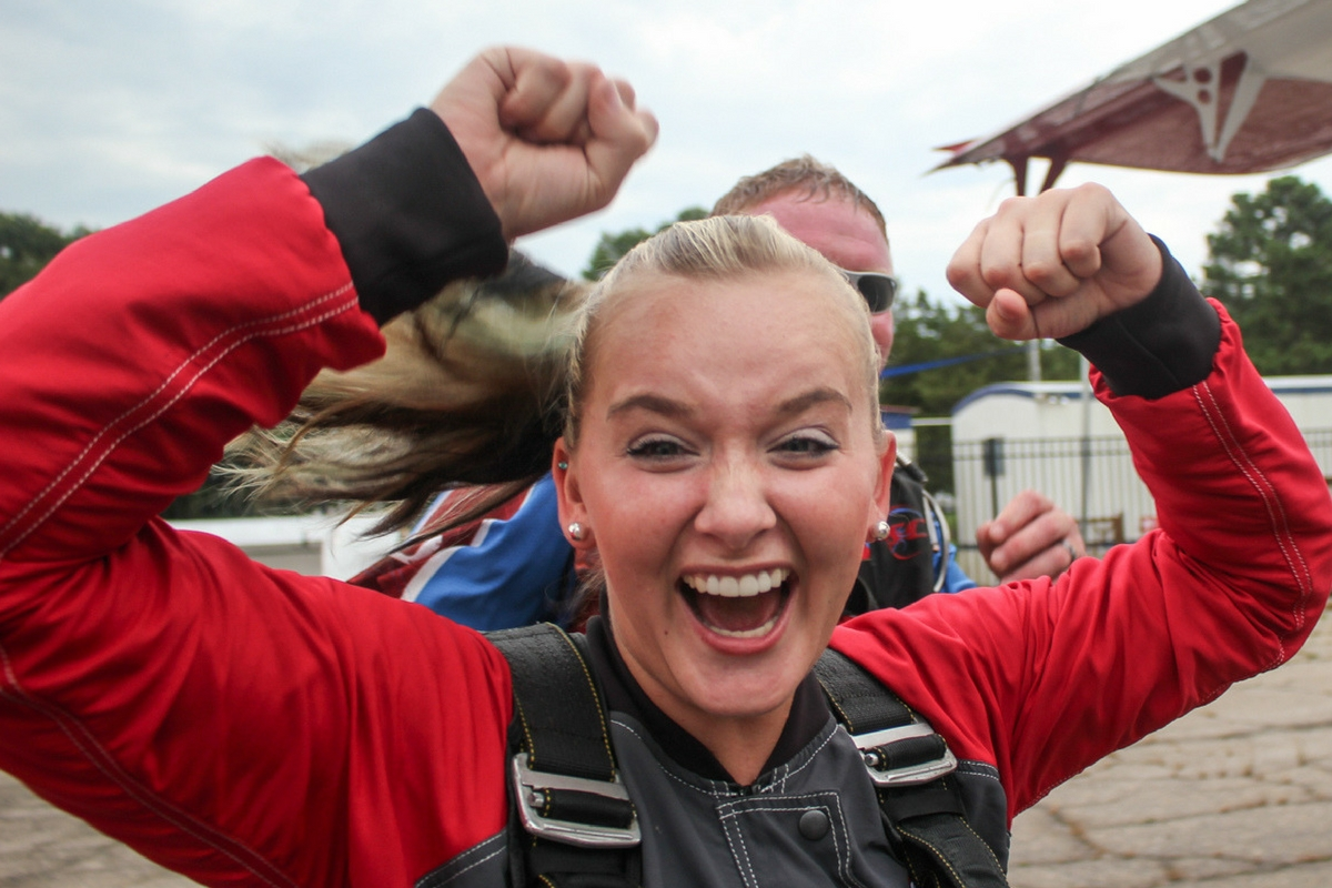 woman smiles before boarding skydiving plane