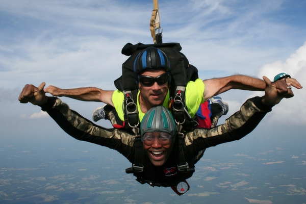 man smiles ear-to-ear in skydiving freefall